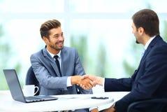 握手的两个企业同事在会议期间 库存照片