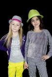 握手的两个可爱的女孩戴逗人喜爱的帽子 免版税库存照片
