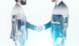 握手的两个商人在一个蓝色城市 免版税库存图片