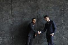 握手的两个商人画象在顶楼 图库摄影