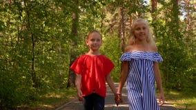 握手的两个女朋友走在夏天公园 走在公园道路的愉快的少年女孩夏日 Frienship 股票录像