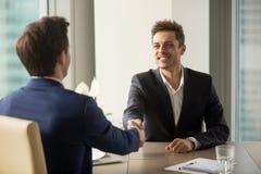 握手的两个快乐的商人,开始工作面试o 免版税库存图片