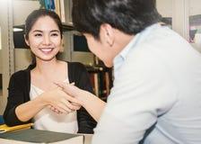握手的两位亚裔大学生在图书馆里 免版税图库摄影