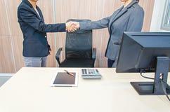 握手的两名女实业家在办公室 免版税图库摄影