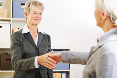 握手的两名年长妇女 免版税库存照片