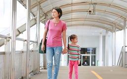 握手的亚裔母亲她的走在天桥的女儿 星期一和儿童一起女孩步行 库存照片