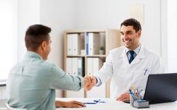握手的医生和男性患者在医院 库存图片