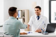 握手的医生和男性患者在医院 库存照片