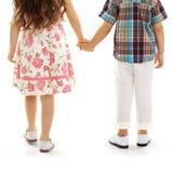 握手的后面观点的小孩在日落 免版税图库摄影