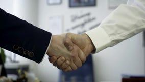 握手的商人作为协议的标志 为两个商务伙伴牢固的握手关闭在办公室 股票录像