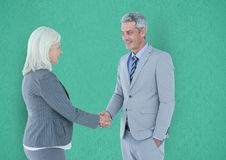 握手的商人反对绿色背景 免版税库存图片