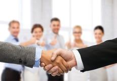 握手的商人和女实业家 免版税库存图片