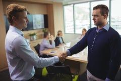 握手的商人在证券交易经纪人行情室 图库摄影