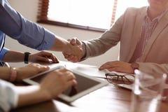 握手的商务伙伴在桌上在见面以后在办公室 图库摄影
