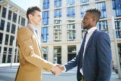 握手的商务伙伴在财政区 免版税库存照片