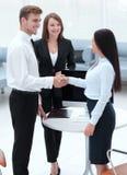 握手的商务伙伴,当站立在办公室的大厅时 库存照片
