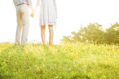 握手的夫妇中央部位背面图,当站立在草反对天空时 免版税库存照片
