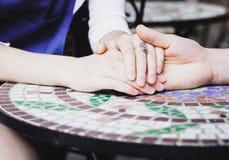 握手的夫妇在桌上 免版税库存图片