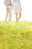 握手的夫妇的中央部位,当站立在草反对天空时 库存照片