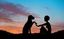 握手的女孩和狗剪影 库存图片