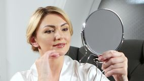 握手的妇女拿着一个镜子和做epilation在她的嘴唇顶部 股票录像