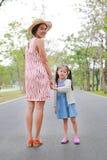 握手的妈妈和女儿在室外自然庭院里 库存照片