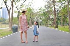 握手的妈妈和女儿在室外自然庭院里 免版税库存照片