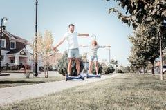握手的宜人的快乐的夫妇乘坐在自平衡的滑行车 免版税库存图片