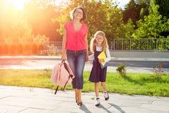 握手的小学的妈妈和女小学生 免版税库存图片