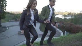 握手的年轻人种间夫妇和攀登小山 股票录像
