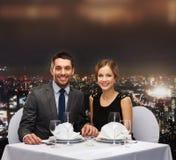 握手的微笑的夫妇在餐馆 免版税库存照片