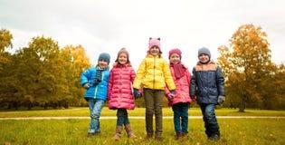 握手的愉快的孩子在秋天公园 库存图片