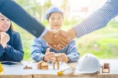 握手的成功的商人建筑师 四个商人建筑师在办公室见面谈论企业项目 库存照片