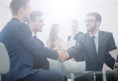 握手的成熟商人密封与他的伙伴的一个成交 免版税库存照片