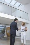 握手的房地产开发商和妇女在新的家 免版税库存图片