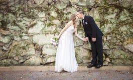 握手的新娘和新郎亲吻在岩石墙壁前面 库存图片