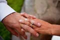 握手的新娘和新郎显示他们的圆环 免版税库存图片