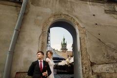 握手的新婚佳偶浪漫夫妇临近wal老的大厦 免版税库存照片