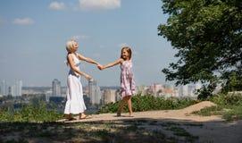 握手的母亲和女儿,走在城市公园 免版税库存照片