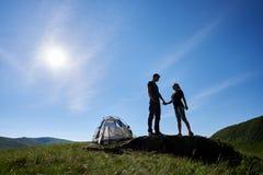 握手的浪漫夫妇剪影站立在石近的帐篷反对蓝天 库存图片