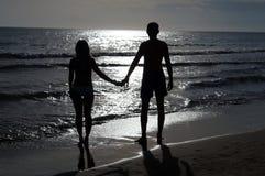 握手的浪漫夫妇在海滩的日落 库存图片