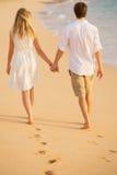 握手的浪漫夫妇走在海滩在日落 免版税库存照片