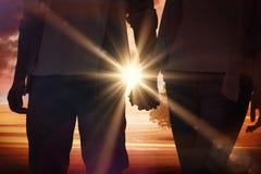 握手的熟悉内情的年轻夫妇的综合图象 免版税库存照片