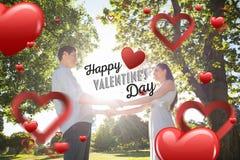 握手的爱恋的年轻夫妇的综合图象在公园 免版税库存图片