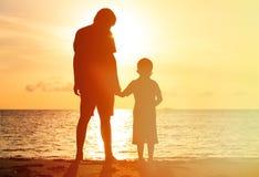 握手的父亲和儿子剪影在 图库摄影