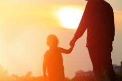 握手的父亲和女儿剪影在日落 图库摄影