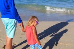 握手的父亲和女儿在与阴影的海滩在沙子 免版税库存图片
