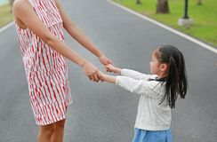 握手的特写镜头妈妈和女儿在室外自然庭院里 免版税图库摄影