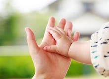 握手的特写镜头父母和婴孩 免版税图库摄影