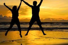 握手的现出轮廓的夫妇跳跃在海滩 库存图片
